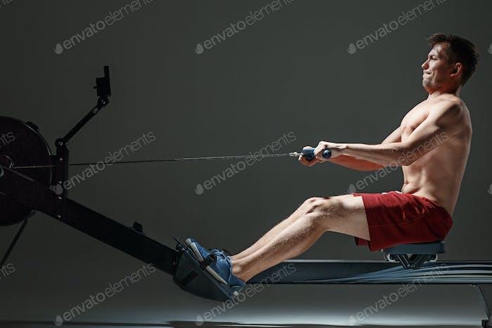 Mann mit einer Presse Maschine in einem Fitness-Club.