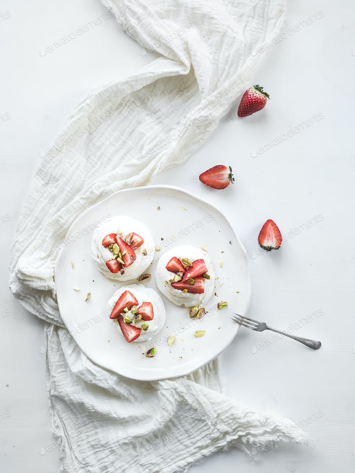Small strawberry and pistachio pavlova meringue cakes