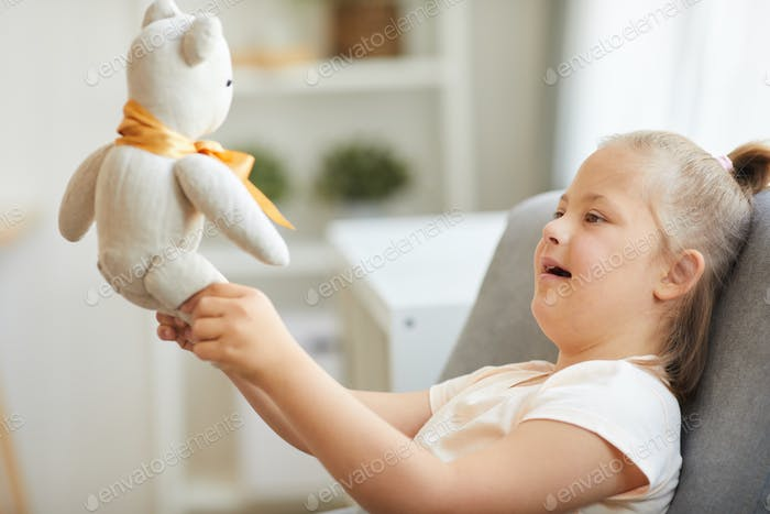 Girl playing with toy bear