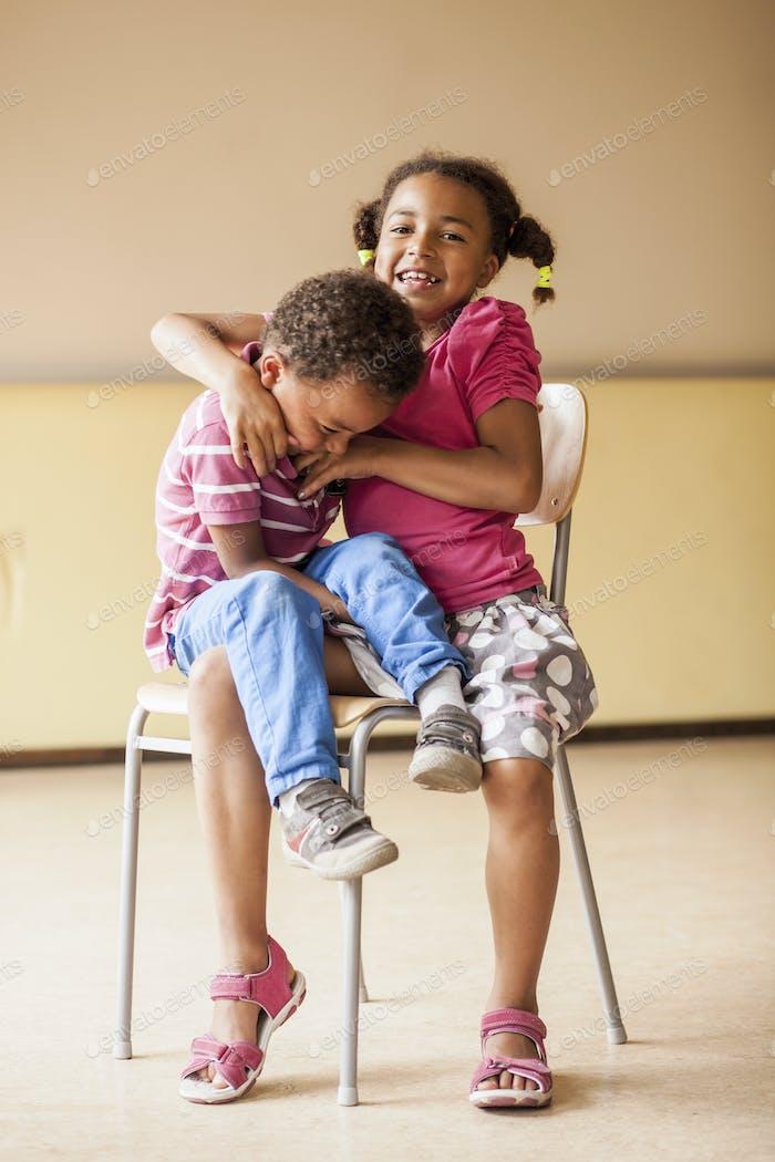 Longitud completa de niña cosquillas niño mientras está sentado en la silla