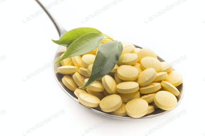 Natural vitamin supplements on the  spoon, isolated on the white.