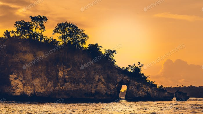 Sunset over the Huge Rock on Beautiful Crystal Bay in Nusa Penida Bali