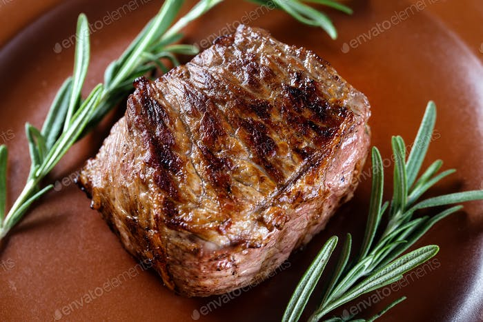 Piece of juicy roast meat with rosemary on a clay plate