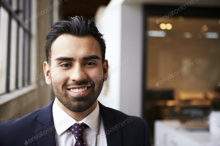 Young Hispanic businessman smiling to camera