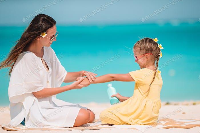 Junge Mutter Anwendung Sonnencreme auf Tochter Nase am Strand. Sonnenschutz