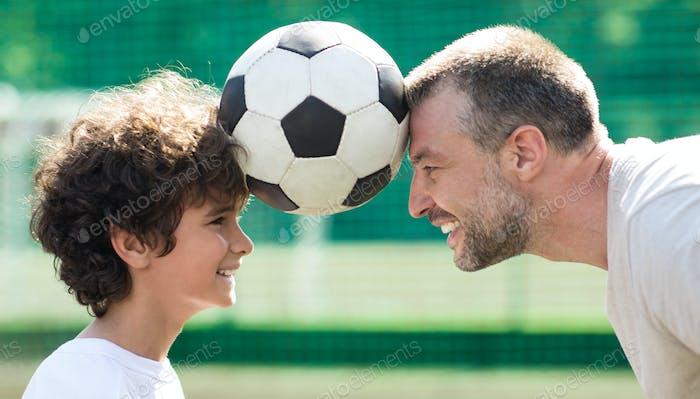 Mann hält Ball zwischen zwei Köpfen mit kleinen Jungen