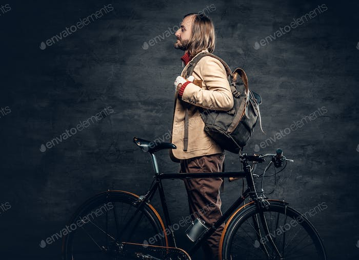 A man posing with bicycle.