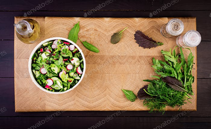 Fresh salad of cucumbers, radishes and herbs. Flat lay. Top view