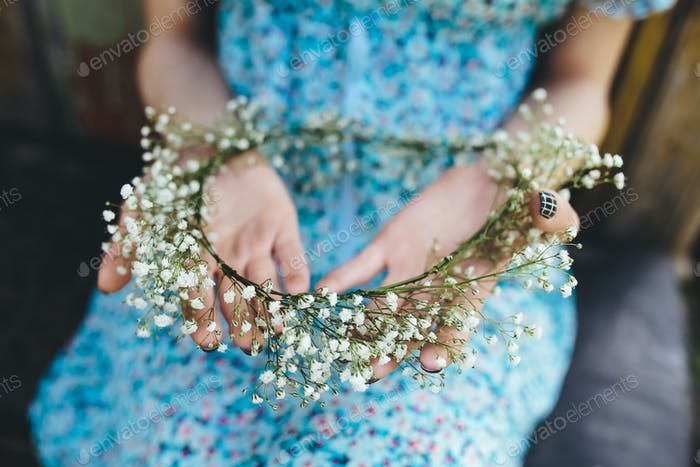 Girl holds head wreath in hands