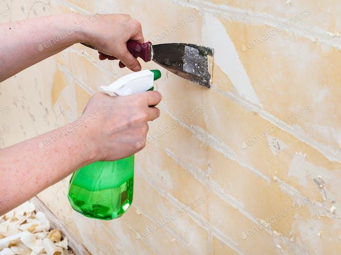 Reinigung der Wand von nassen alten Tapeten mit Spatel