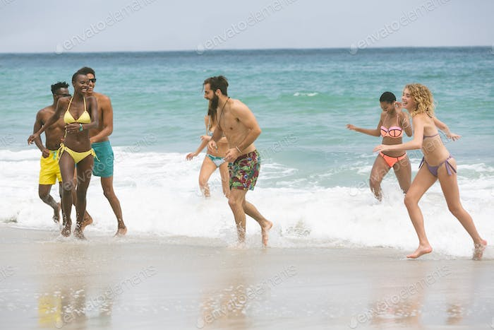 Front view of multi ethnic group of friends enjoying and having fun on water at beach on sunny day