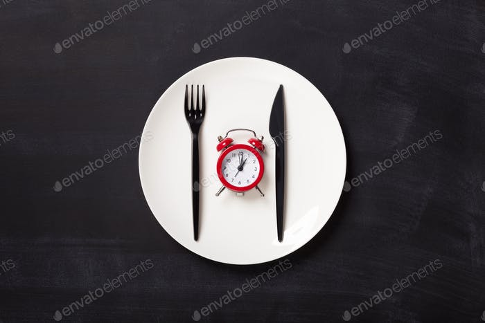 Top view on plastic forks and clock on white plate at black background