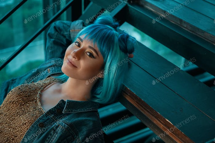 Stylish woman wearing a blue wig laying on stairs  looking to c