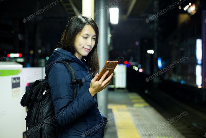Woman use of cellphone and standing at Tokyo city staton