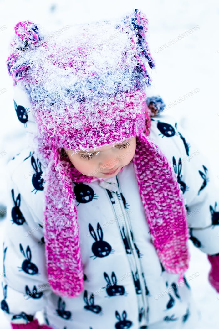 Child in snowy day. Portrait of baby girl in white snow suit and pink hat in the winter park.  in .