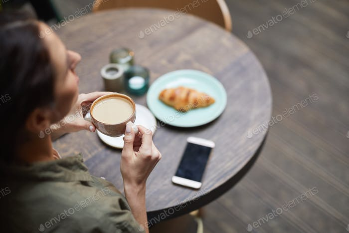 Above View of Young Woman Enjoying Coffee