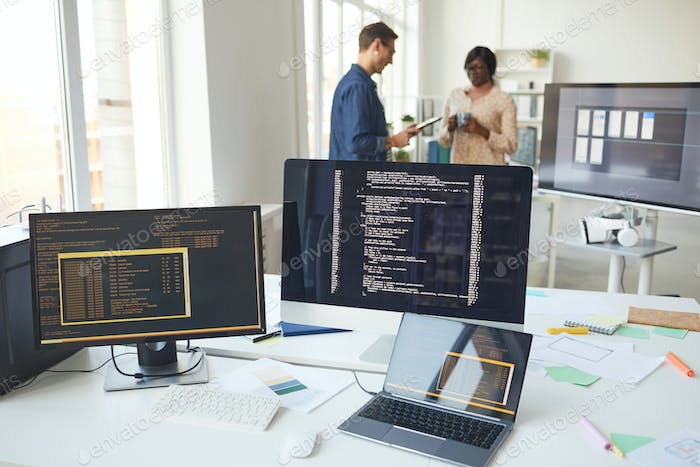 Computers with Code on Screen in IT Office