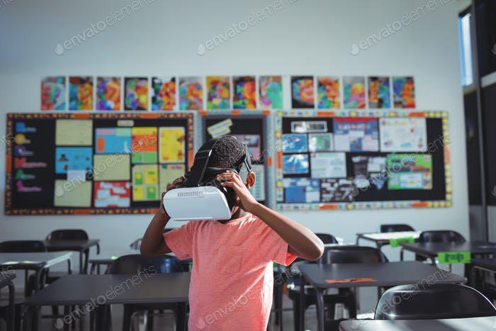 Boy wearing virtual reality simulator against wall