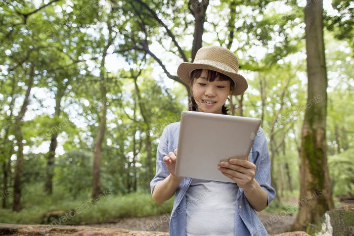 Young woman holding a digital tablet in a forest.
