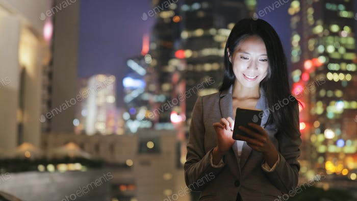 Business woman using cellphone in city at night