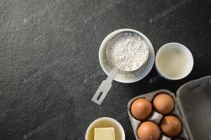 Directly above shot of flour and egg carton