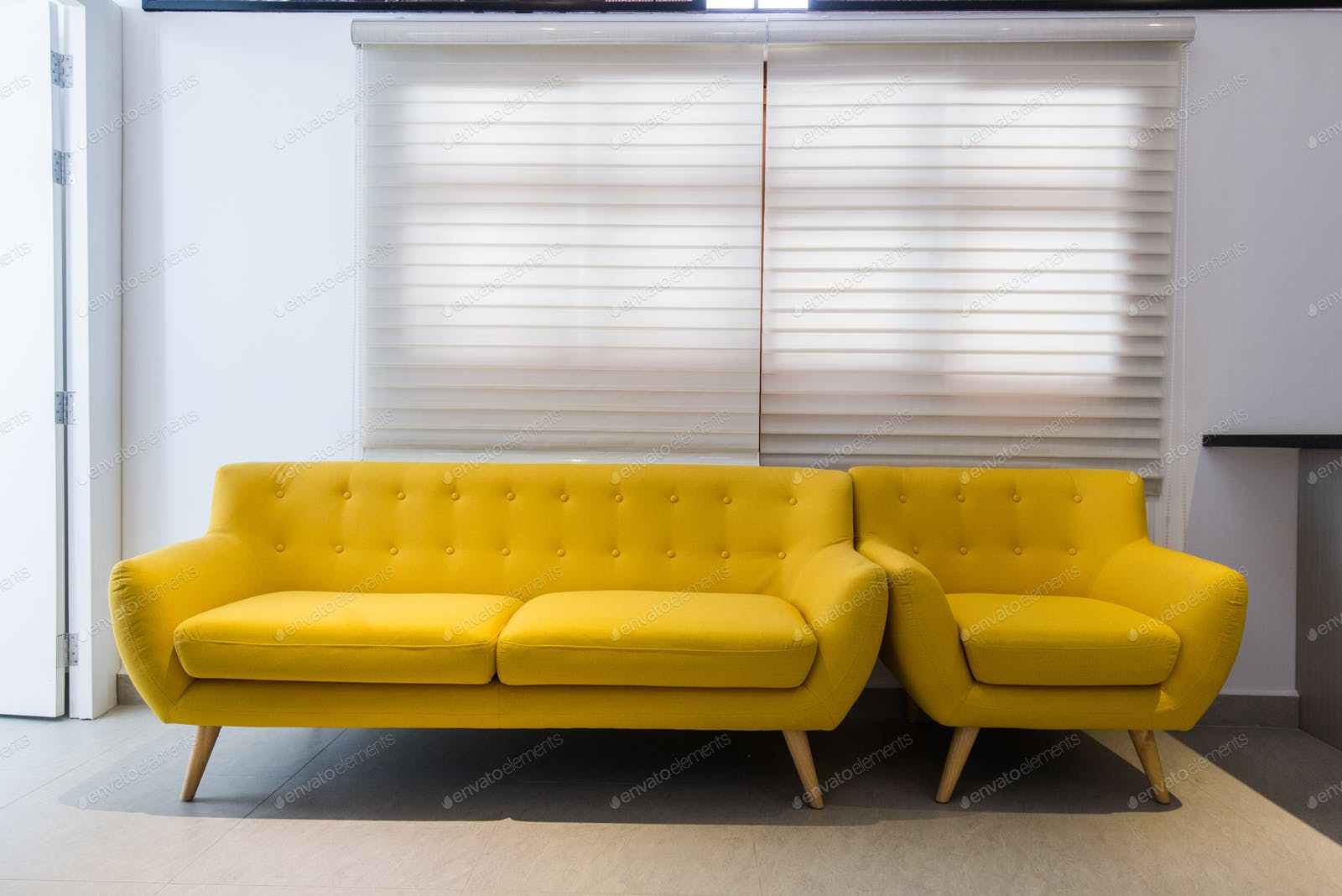 Modern yellow sofa and chair in room interior at home or hotel photo by  romankosolapov on Envato Elements
