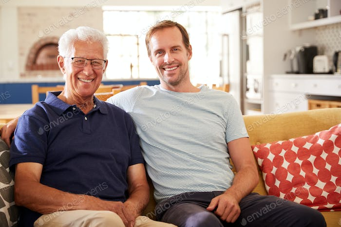 Portrait Of Smiling Father With Adult Son Relaxing On Sofa At Home