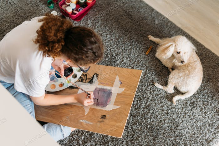 Curly hair girl teenager in white t-shirt painting on wooden desk with poodle dog