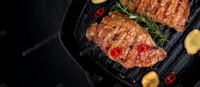 Banner von Gegrilltem Schweinefleisch Steak in Grillpfanne