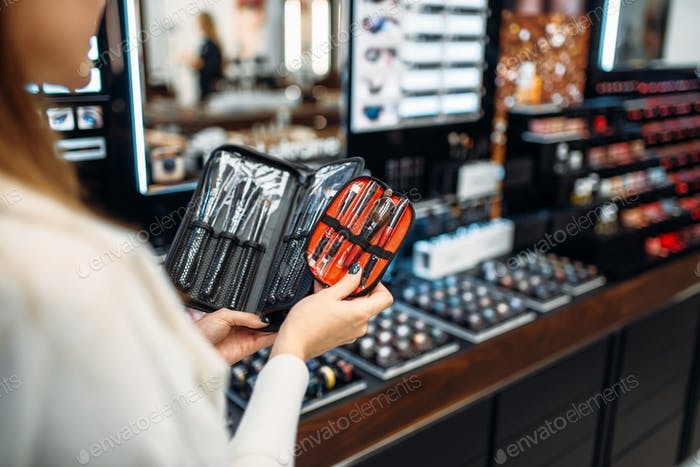 Customer choosing cosmetics tools in makeup shop