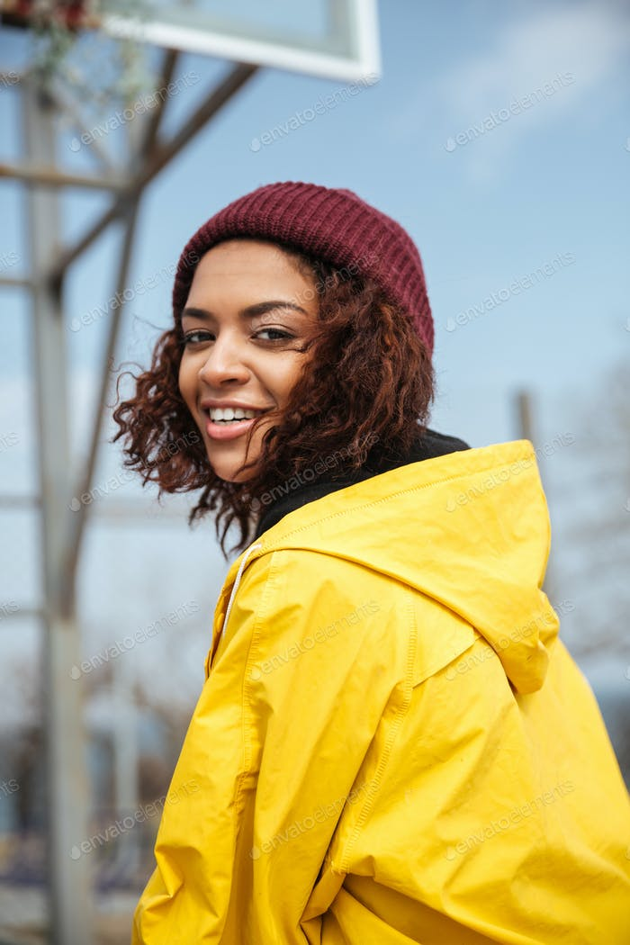 Smiling african curly young lady wearing yellow coat
