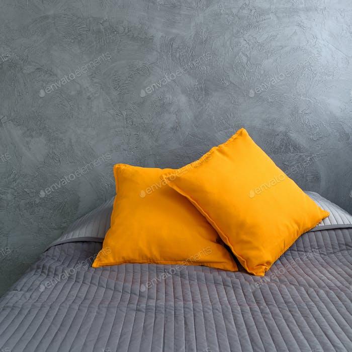 Graues Bett und orangefarbene Kissen