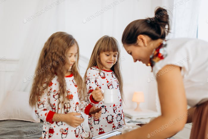 Young mother is bringing cocoa with Marshmallows and cookies to her daughters in pajamas sitting on