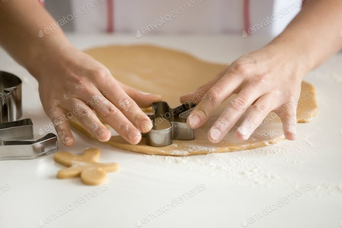 Close up of professional confectioner hands cutting gingermen