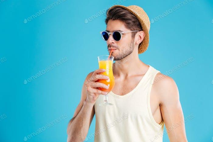 Handsome man in hat and sunglasses drinking fresh orange juice
