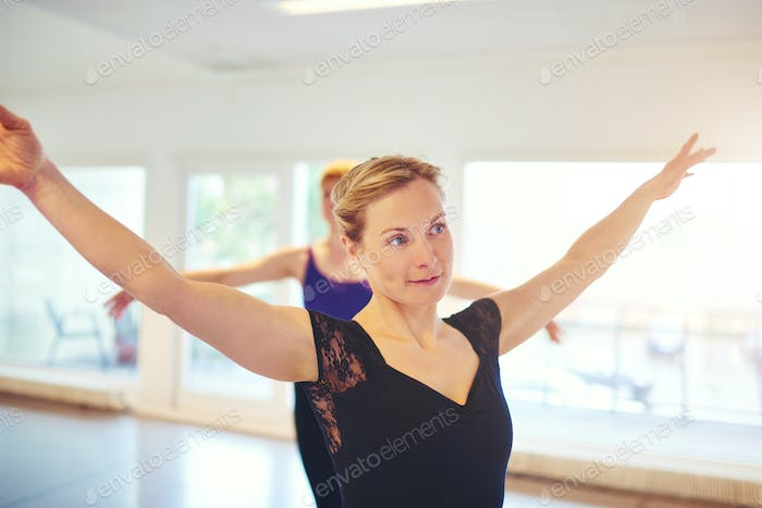 Pretty woman posing while dancing ballet in group