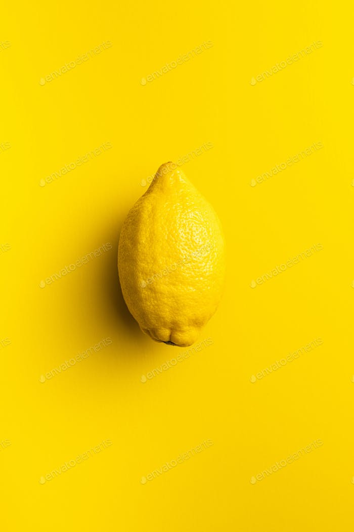 Yellow lemon fruit on yellow background.