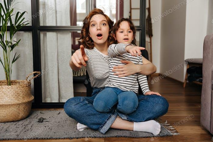 Mamá e hija en jeans idénticos y camisetas están mirando a la cámara en sorpresa y mostrando