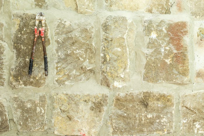 Old moldy stone wall with work scissors.
