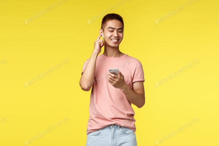 Technology, communication and lifestyle concept. Handsome asian man using mobile phone and wireless