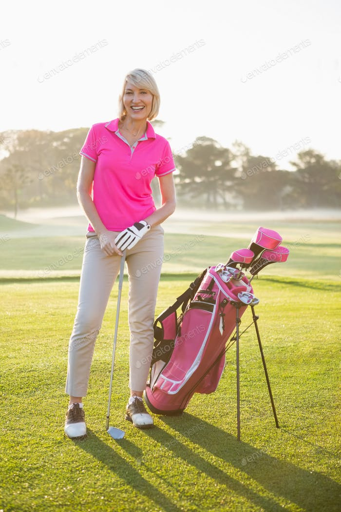 Woman golfer posing with her golf equipments