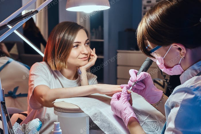 Pretty dreamy woman got nail care from young manicurist.