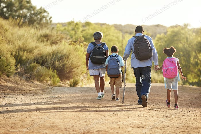 Rear View Of Grandparents With Grandchildren Wearing Backpacks Hiking In Countryside Together