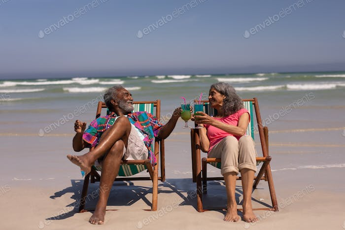 Senior couple relaxing on sun lounger and toasting cocktail glasses on beach in the sunshine