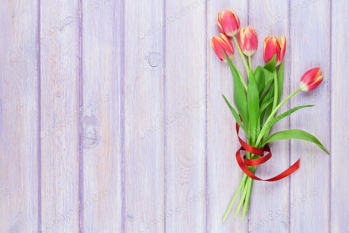 Red tulips on wooden table
