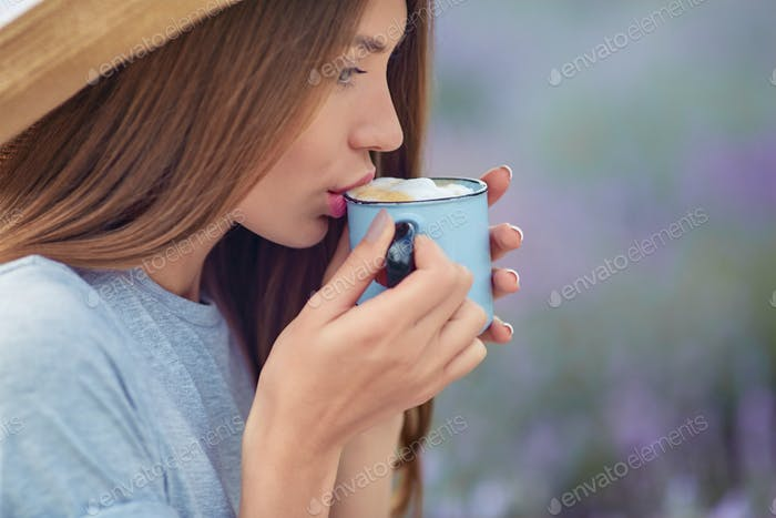 Young woman drinking coffee in lavender field