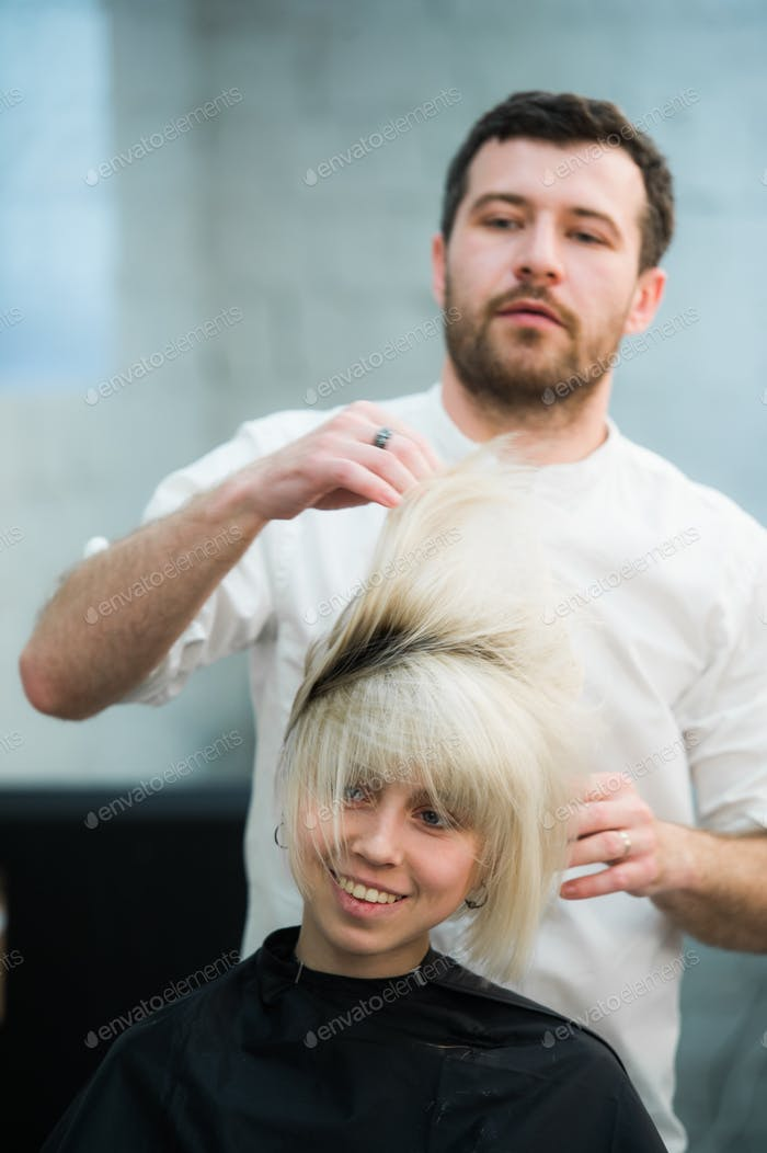 male hairdresser puts woman's hair in a hairdressing salon
