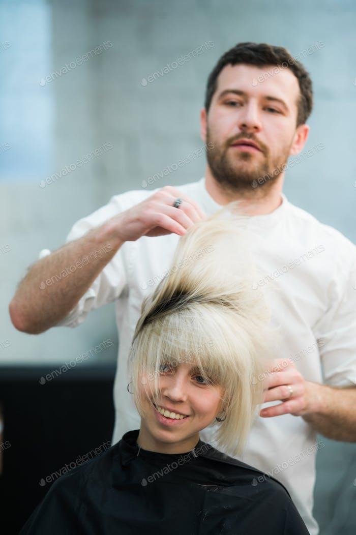 männlicher Friseur stellt Frauenhaare in einen Friseursalon