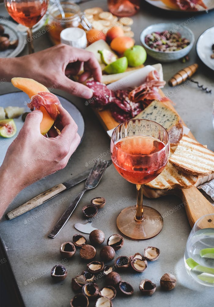 Rose wine, cheese, charcuterie, appetizers and mans hands with food