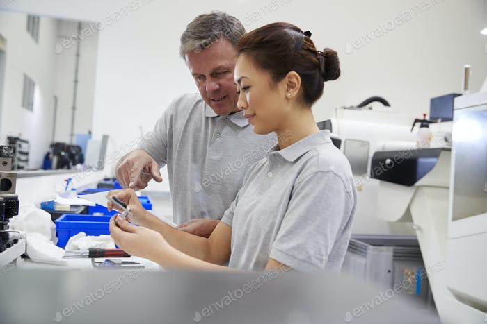 Engineer And Female Apprentice Measuring Components In Factory